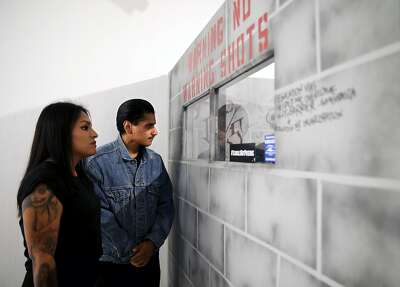 "Daniel Casillas, 22, and his sister, Elisabeth Casillas, 28, look at a facsimile solitary confinement cell built by Martin Leyva as they attend the 2nd Annual Project Rebound Mural Celebration called ""Incarceration to Liberation"" at San Francisco State University."