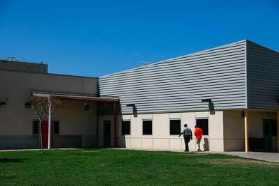 An incarcerated youth is escorted by a probation officer as he walks across the grounds at the Fresno County juvenile hall in Fresno.