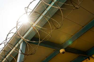 Security at the Fresno County juvenile hall includes barbed wire and a surveillance camera.
