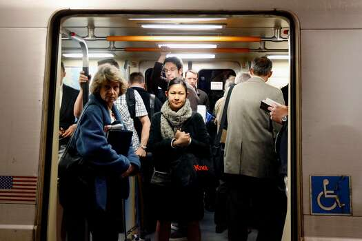 Commuters at Embarcadero Station crowd into a BART car in San Francisco, California.