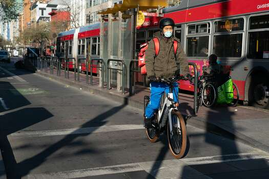 One bicyclist wearing a protective mask waits at a light on Market St. on Thursday, March 19, 2020, in San Francisco, California.