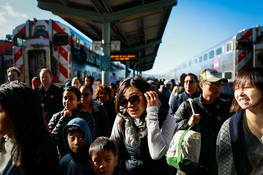 A crowd of people walk through the Fourth and King Street Caltrain station in San Francisco, California, on Monday, Jan. 21, 2019.