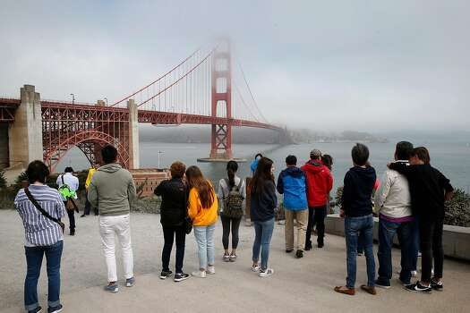 A crowd of visitors snap pictures of the Golden Gate Bridge in San Francisco, California, on Friday, Aug. 3, 2018.