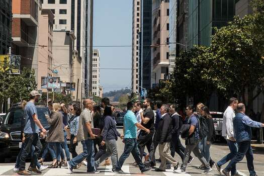 A large group of San Francisco workers, residents and tourists cross Mission Street at New Montgomery in the South of Market district of San Francisco, California, on Friday, July 20, 2018.