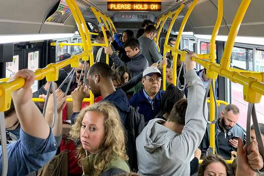 Riders pack onto a very crowded Muni bus as it makes its way down Market Street in San Francisco, California, on Tuesday, July 18, 2019.