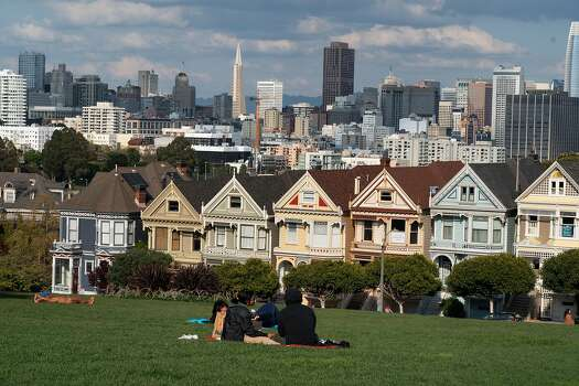 Just a few people in Alamo Square next to the Painted Ladies, Victorian and Edwardian houses and buildings, on March 19, 2020 in San Francisco, California.