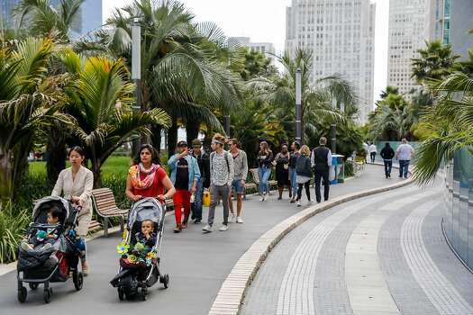 Just under 20 people walk along the pathway of Salesforce Park on Monday, July 1, 2019, in San Francisco, California.
