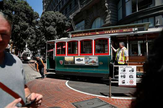 Workers rotate a cable car at the Powell Street cable car turnaround on Friday, August 30, 2019 in San Francisco, California.