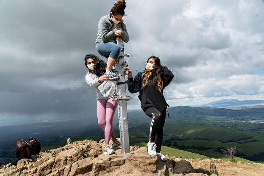 Three people, wearing protective masks, get set up for a photo at Mission Peak on Thursday, March 26, 2020, in Fremont, California.