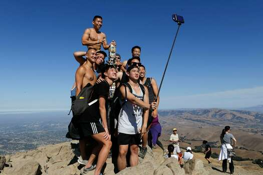 A large group of friends gather for a selfie at the summit post atop Mission Peak above Fremont , California, on Saturday Sept. 13, 2014.