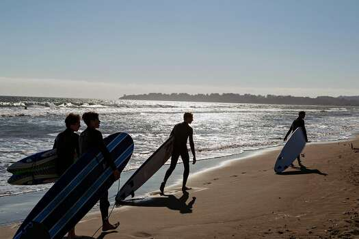 Four surfers drag their boards behind them as they walk on Stinson Beach in Marin County on Saturday, May 23, 2015.