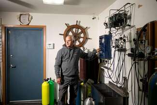 Keith Cormican fills air tanks in his scuba dive shop, Wazee Sports Center, in Black River Falls, Wisconsin.