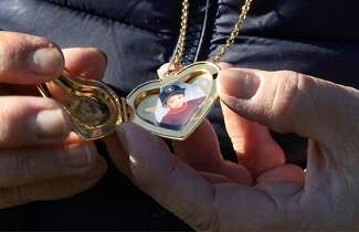 Jeannie Altienza holds a locket with a photo of her son Laudermer Arboleda during a November visit to his grave at Chapel of the Chimes Memorial Park in Hayward.