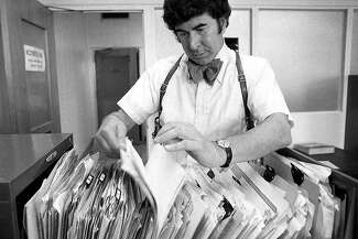 Inspector David Toschi rifles through files. He is wearing a bow tie.