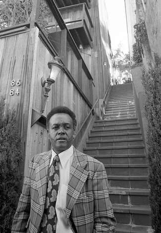 Portrait of Rotea Gilford at a crime scene, wearing a plaid jacket and paisley tie.