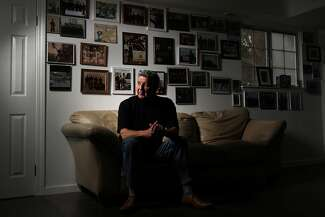 Bob Del Torre sits on a couch with his hands clasped together.