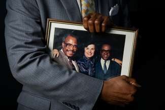 Marcus Sanders holds a framed photograph of his father, Earl Sanders, with Dianne Feinstein and Rotea Gilford.
