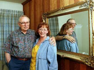 Frank Worthen stands with his arm around his wife, next to a large mirror with an ornate gold frame.