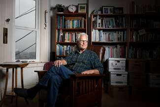 Jim Van Burskirk sits in a brown leather chair in his home. The shelves behind him are filled with books.