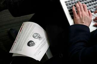 A reporter types of a laptop computer while sitting next to an age-enhanced sketch of a man San Francisco Police believe to be the Doodler.