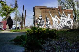 Photographed at ground level, a mural emerges behind a plot of grass, daffodils and debris. A person walks by on the sidewalk.
