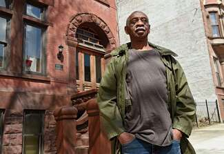 Bouldin, in a green jacket, stands in front of a historic brownstone.