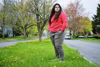 Photo of Jasmine Higgins standing on a grassy median near her home in the Pine HIlls neighborhood of Albany.