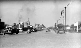 Black and white photo of cobblestone street, with early automobiles driving on it. Off in the distance is what is nowthe SUNY System Administration building.