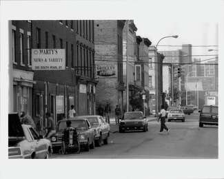 Black and white photo of South Pearl Street. People are pictured walking, and standing near parallel parked cars.