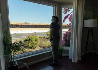 Dan Stys looks out the window of his mother-in-law's rental home in May as he prepares it for new tenants on Beach Park Boulevard in Foster City. The steel plates that form the backbone of a rebuilt and taller levee can be seen across the way.