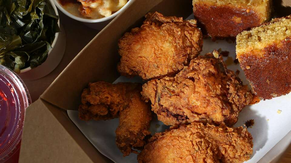 Golden fried chicken with squares of corn bread in a takeout box