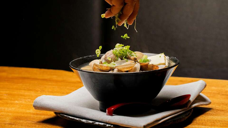 A hand sprinkles toppings into a black bowl of clam ramen.