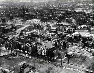 Black-and-white photo shows city streets with clusters of row houses and churches, as well as many cleared plots of land.
