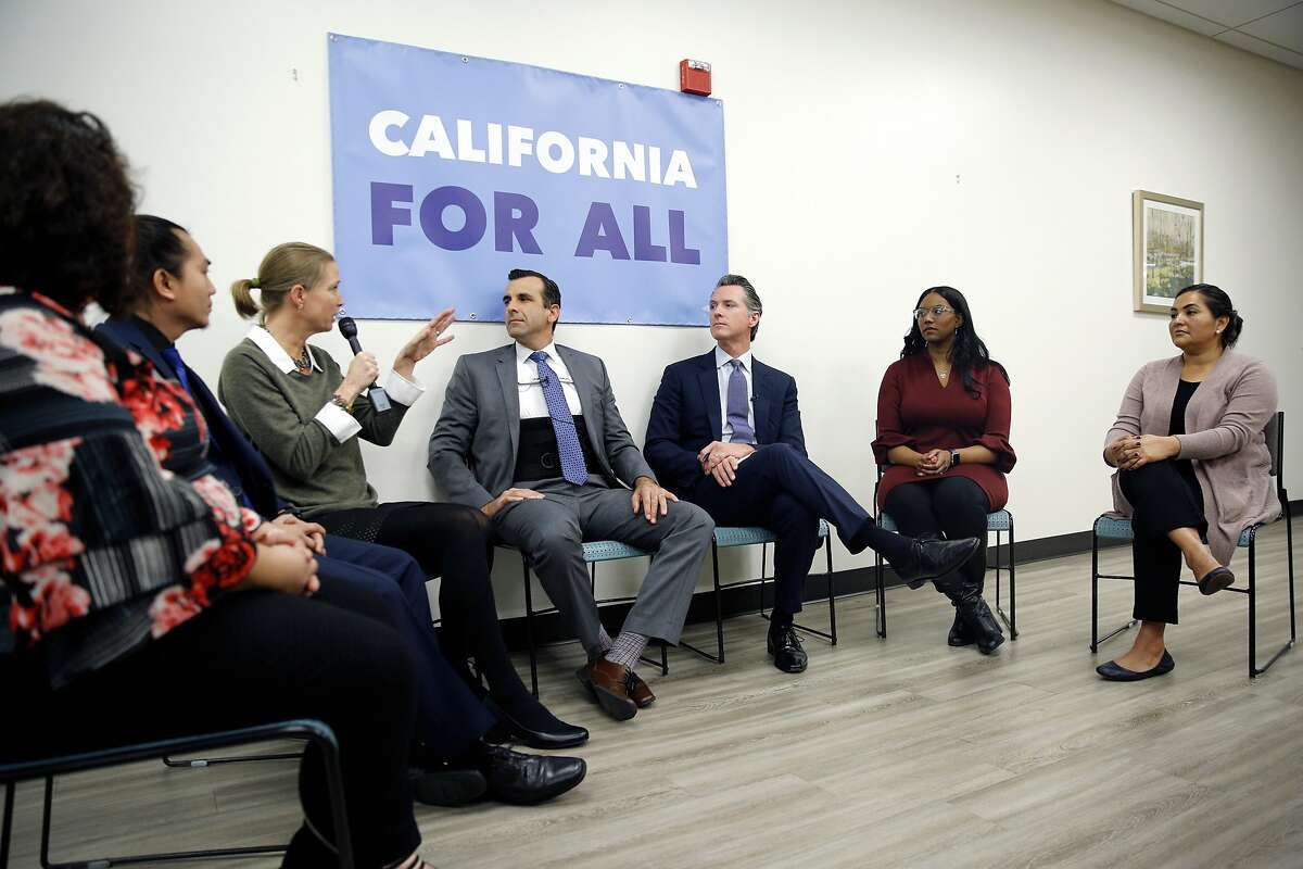 Pizza Bocca Lupo owner Jenneke de Vries (on the microphone) chats with San Jose Mayor Sam Liccardo and Gov. Gavin Newsom during a community meeting at the Seven Trees Community Center on Tuesday, Jan. 15, 2019, in San Jose, Calif. The politicians met with people who are grappling with the state's housing crisis. At the event, the governor talked about housing proposals he laid out in the budget he submitted to the Legislature last week.