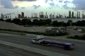 A truck passes by a portion Exxon Mobil's Baytown refinery.