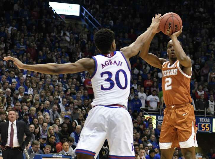 Texas guard Matt Coleman, right, puts up a shot over Kansas' Ochai Agbaji during a game that goes down to the wire Monday.