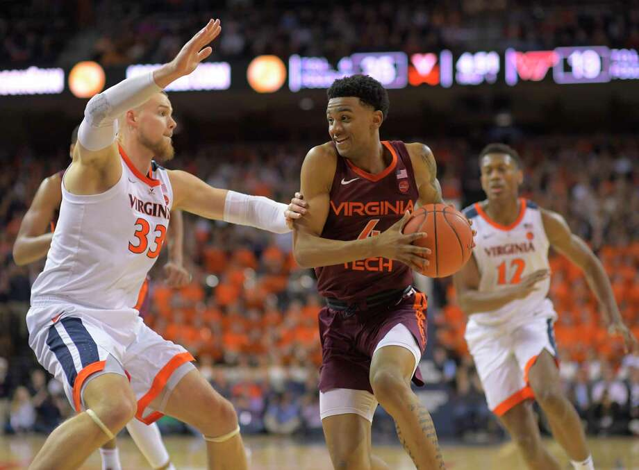 Virginia center Jack Salt (33) defends Virginia Tech guard Nickeil Alexander-Walker (4) during their game Tuesday night at John Paul Jones Arena in Charlottesville. Alexander-Walker had 19 points for the No. 9 Hokies, who fell to the No. 4 Cavaliers, 81-59. Photo: Washington Post Photo By John McDonnell / The Washington Post