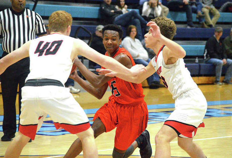 Edwardsville senior Jaylon Tuggle, middle, tries to get past two Highland defenders during the second quarter of Tuesday's game at the Jersey Mid-Winter Classic. Photo: Scott Marion/Intelligencer