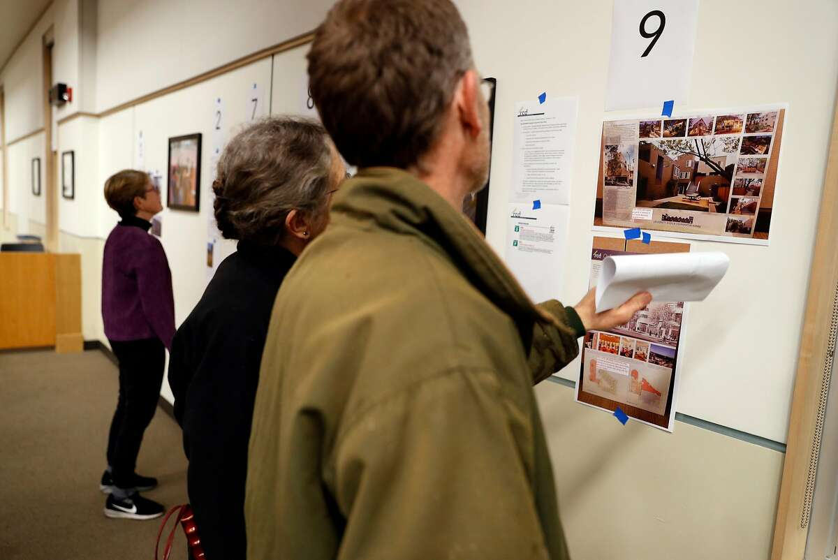 Community members look at some of the twenty five proposals submitted for housing at North Berkeley BART station before Berkeley City Council meeting in Berkeley, Calif., on Tuesday, January 15, 2019.