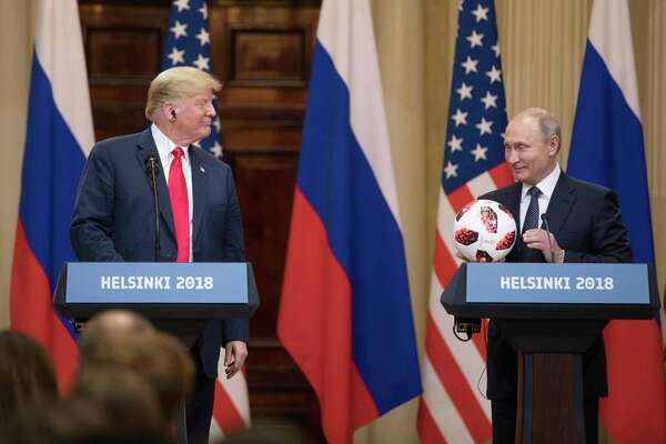 President Donald Trump smiles while Vladimir Putin, Russia's president, holds a football during a news conference in Helsinki, Finland, on July 16, 2018.