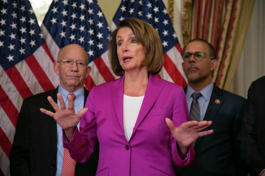 Speaker of the House Nancy Pelosi, D-Calif., flanked by Rep. Peter DeFazio, D-Ore., left, and Rep. Anthony Brown, D-Md., talks to reporters after signing a House-passed a bill requiring that all government workers receive retroactive pay after the partial shutdown ends, at the Capitol in Washington, Friday, Jan. 11, 2019. Photo: J. Scott Applewhite, AP / Copyright 2019 The Associated Press. All rights reserved.