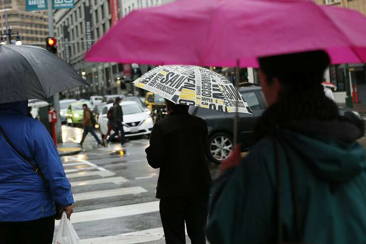 People make their way through the rain in downtown on Tuesday, Jan. 15, 2019, in San Francisco, Calif.