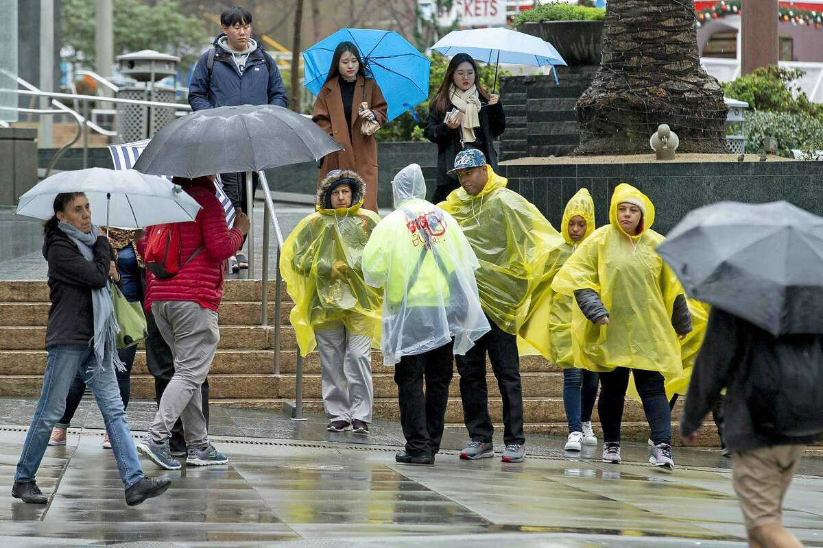 People make their way through the rain at Union Square on Tuesday, Jan. 15, 2019, in San Francisco, Calif.