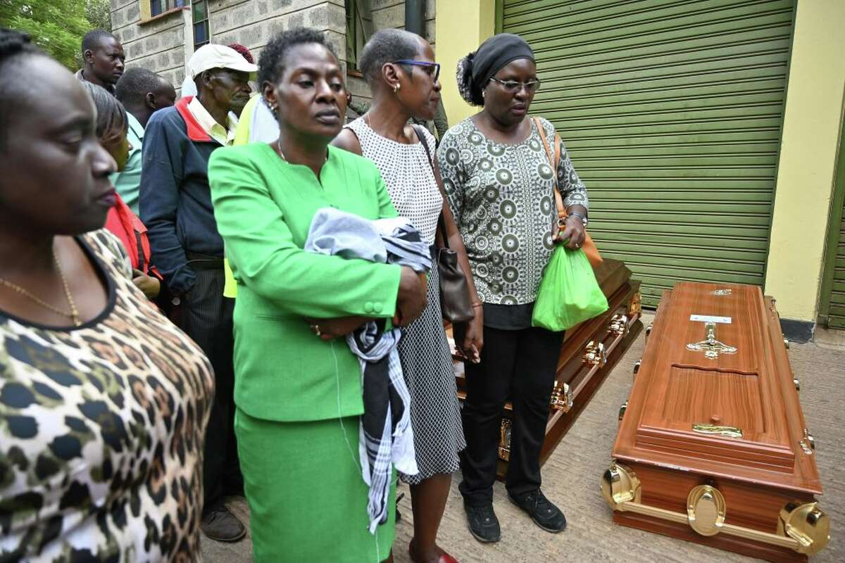 Relatives stand next to empty coffins at the Chiromo mortuary in Nairobi, Kenya on January 16, 2019 after a blast followed by a gun battle that rocked the upmarket hotel complex the day before. - Kenyan President Uhuru Kenyatta said on January 16, 2019 that all Islamists who had stormed an upmarket hotel complex had been