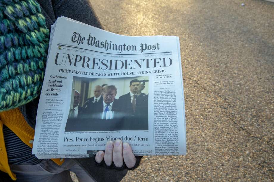 "Volunteers distribute a lookalike ""special edition"" of The Washington Post, date May 1, which predicts Trump leaving office after months of women-led protests on January 16, 2019 in Washington, DC. Photo: Tasos Katopodis/Getty Images For Yes Labs"