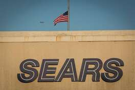 An American flag flies at half-staff above a Sears store in San Bruno, Calif., on Dec. 28, 2018.