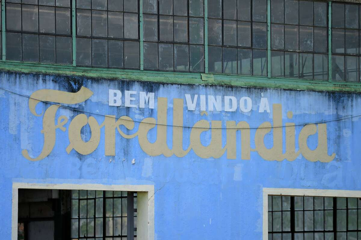 A welcome sign on the side of an abandoned factory building near the Fordlandia harbor on July 5, 2017 in Aveiro, Brazil. American industrialist Henry Ford negotiated the rights to 2.5 million acres of land from the Brazilian government to establish a rubber plantation. Construction started in 1926 with the hopes of employing 10,000 workers. By 1945 the project was considered a failure and the land was given back to the Brazilian government. (Photo by Joel Auerbach/Getty Images)