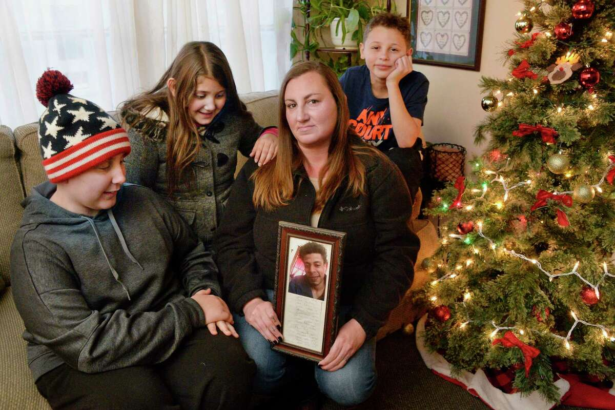 Kristen Hickey holds a photo of her deceased fiancee Justus Booze, with her children, from left, Matthew Schutta, 13, Olivia Torres, 9 and Joshua Ramos, 11, in their living room Wednesday Dec. 5, 2018 in Ballston Spa, NY. They still take care of Boozee, the gray tabby cat Justus rescued from cruel people. (John Carl D'Annibale/Times Union)