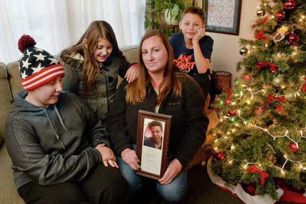 Kristen Hickey holds a photo of her deceased fiancee Justus Booze, with her children, from left, Matthew Schutta, 13, Olivia Torres, 9 and Joshua Ramos, 11, in their living room Wednesday Dec. 5, 2018 in Ballston Spa, NY. (John Carl D'Annibale/Times Union)