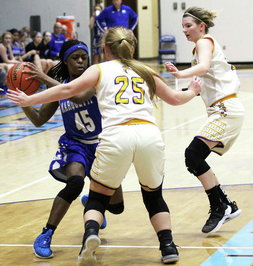 Marquette Catholic's Adrenna Snipes takes the ball to the basket against two Taylorville defenders during a Dec. 27 game at the Jersey Holiday Tourney. On Tuesday in Edwardsville, Snipes scored 20 points in the Explorers' victory over Metro-East Lutheran. Photo: Greg Shashack / The Telegraph